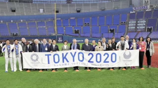 people holding a sign for tokyo 2020 inside the yokohama baseball stadium. - sport点の映像素材/bロール