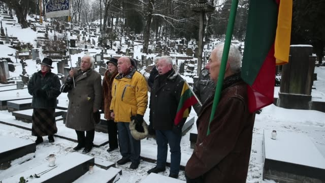 People holding Lithuanian flags sing at a grave at Rasos Cemetery to honor signatories of the 1918 Independence Act during the 100th anniversary of...