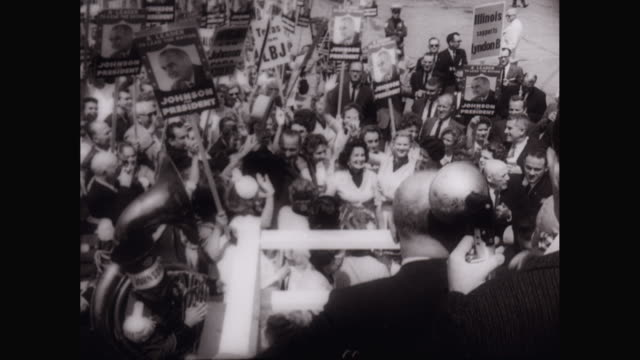 vídeos de stock, filmes e b-roll de ws people holding placards and cheering, politician - lbj - being interviewed at political rally / unites states - comício político