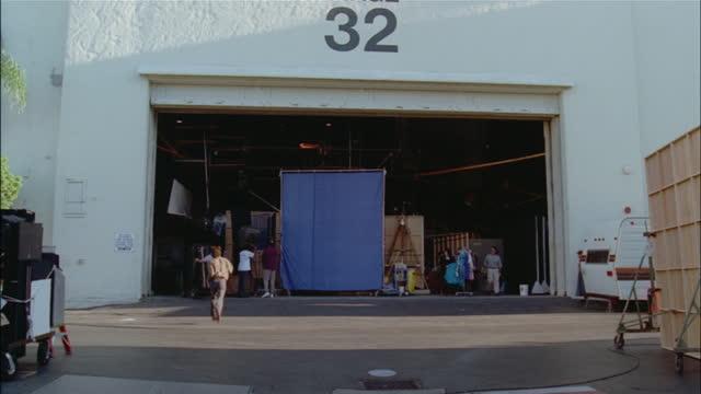 vidéos et rushes de people hustle around a movie set. - décor de cinéma