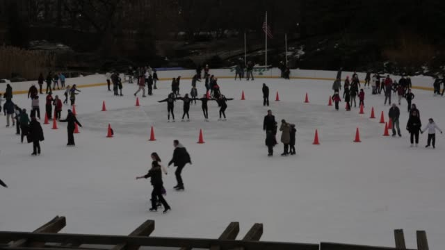 people ice skate at the trump skating rink in central park on february 2, 2014 during the day, a tight shot of people skating away from the camera, a... - ice skating stock videos & royalty-free footage