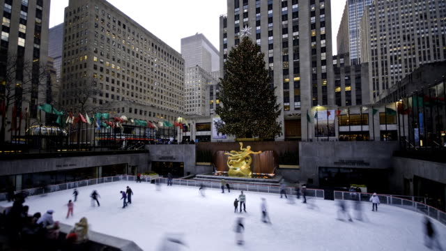 people ice skate in rockefeller plaza in new york city. - rockefeller center video stock e b–roll