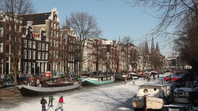 stockvideo's en b-roll-footage met people ice skating on frozen canal called keizersgracht. amsterdam, netherlands - gemengde leeftijdscategorie