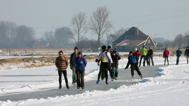 people ice skating on polder canal in front of farm - polder stock videos and b-roll footage