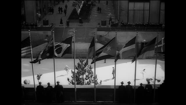 vídeos de stock, filmes e b-roll de people ice skating on sunken central plaza rink w/ people lining upper edge watching tops of united nations members country flags flying fg steps to... - pista de patinação no gelo