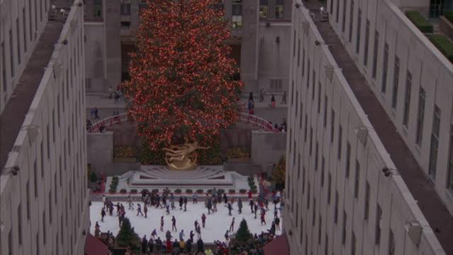 people ice-skate in new york city's rockefeller center. - rockefeller center christmas tree stock videos & royalty-free footage