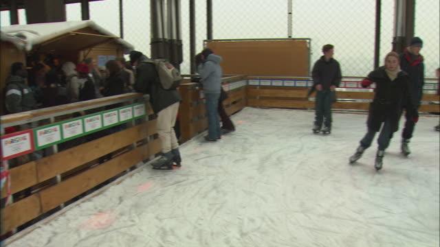 ws pan people ice-skating under eiffel tower / paris, france - エッフェル塔点の映像素材/bロール