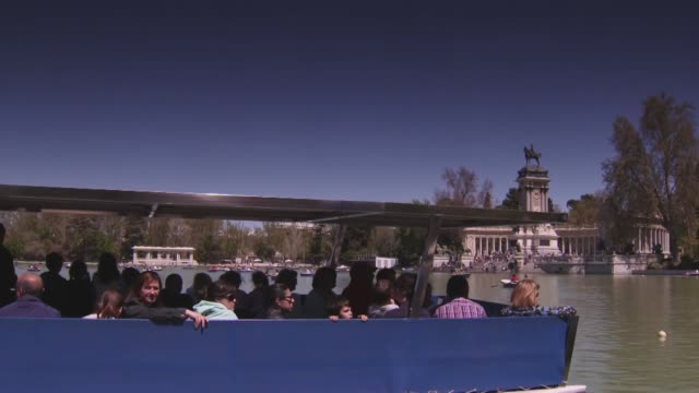 people in a boat on lake in front of monument to alfonso xii of spain in buen retiro park in central madrid, spain - ruderboot stock-videos und b-roll-filmmaterial