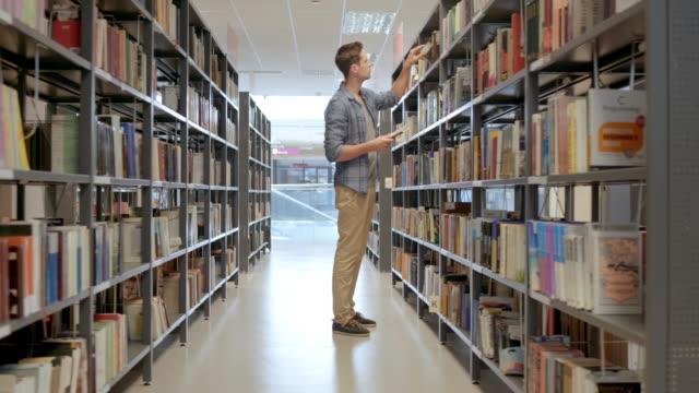 DS Personen in der öffentlichen Bibliothek der Suche nach Büchern auf dem Regal