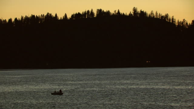 ws aerial people in boat in flathead lake at dusk with orange sky / montana, united states - flathead lake stock videos and b-roll footage