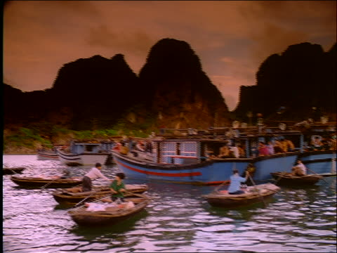 pan of people in boats by mountainous coast / vietnam - cinematography stock videos & royalty-free footage