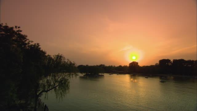 stockvideo's en b-roll-footage met ws ha tu people in boats on lake houhai at sunset, beijing, china - waterfiets
