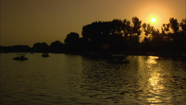 stockvideo's en b-roll-footage met ws people in boats on lake houhai at sunset, beijing, china - waterfiets