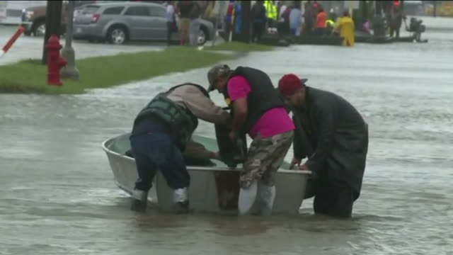 people in boats, walking through water on flooded streets after hurricane harvey near the intersection of wallisville road and uvalde road in houston... - soccorritore video stock e b–roll