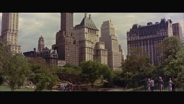 ws people in central park with buildings at 59th street and 5th avenue in background / new york city, new york state, united states - new york city 1950s stock videos & royalty-free footage