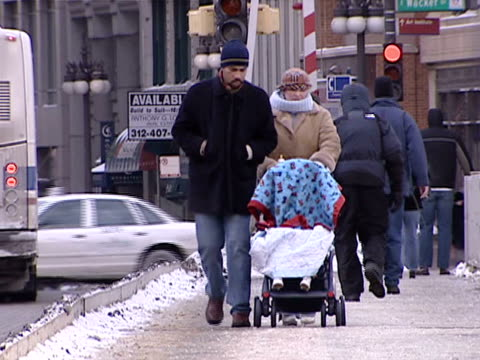 People in coats walk around in cold winter weather on Michigan Avenue on January 20 2004 in Chicago Illinois