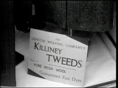 vídeos de stock e filmes b-roll de people in coats walking sidewalk in front of store cu sign below coat 'killiney tweeds' 'irish wool' sign on rolled blanket salesman showing woman... - 1944