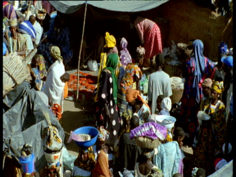 People in colourful clothes carry goods on heads at busy ancient market at Djenne, Mali