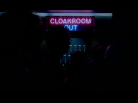 People in concert venue walk past illuminated neon cloakroom sign
