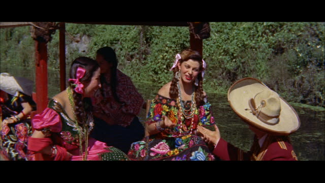 ms people in costumes in flowered boats / mexico - anno 1957 video stock e b–roll