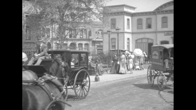 people in costumes sitting in horse drawn carriage as man in foreground holds up clapboard / horse-drawn carriage and wagon parked on street pulling... - xix secolo video stock e b–roll