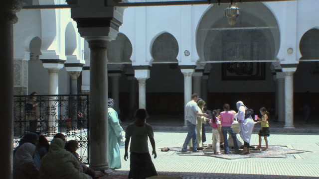 ws pan people in courtyard of moulay idriss mosque, fez, morocco - モロッコ文化点の映像素材/bロール