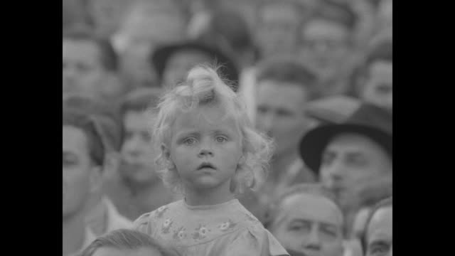 vs people in crowd little blond girl intently looks at camera blond woman others looking a camera and clapping hands - 1951 bildbanksvideor och videomaterial från bakom kulisserna
