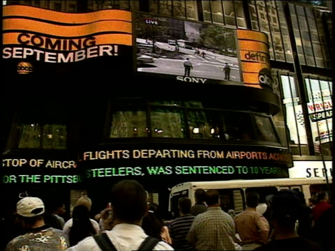 people in crowd looking up at news headlines on zipper sign & footage of people fleeing wtc on large video projection screen hours after attack;... - 2001 stock videos & royalty-free footage