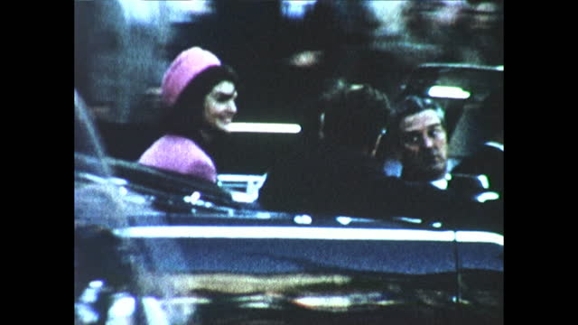 / people in dallas waiting for jfk to pass by / jfk and jackie kennedy in convertible talking to governor john connally moments before jfk's... - attentat auf john f. kennedy stock-videos und b-roll-filmmaterial
