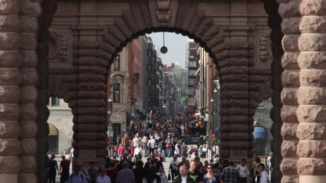 ms people in drottninggatan, view through arch of riksdagshuset / stockholm, stockholm, sweden - sweden stock videos & royalty-free footage