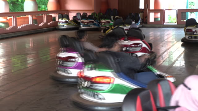 stockvideo's en b-roll-footage met people in face masks driving bumper cars in amusement park during covid-19 pandemic, in dunia fantasi theme park inside ancol taman impian. the... - botsauto
