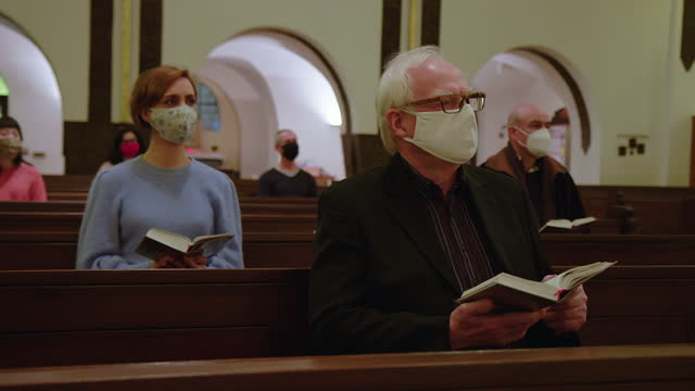 people in face masks during religious mass at church - church stock videos & royalty-free footage