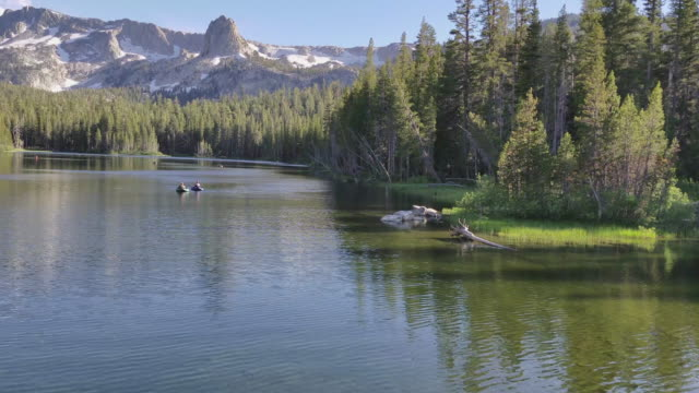 4k - people in float tubes fishing on a mountain lake snow capped mountains against a clear blue sky - mammoth lakes video stock e b–roll