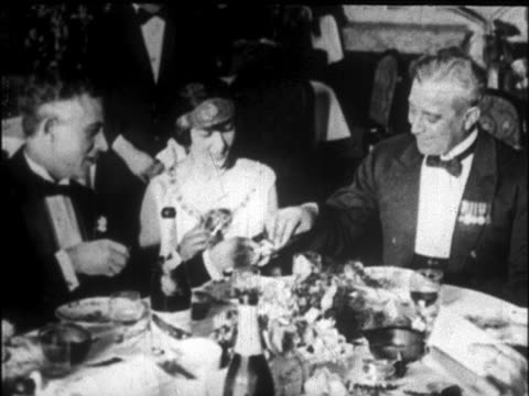 B/W 1926 people in formalwear smoking at dinner table on cruise ship / newsreel