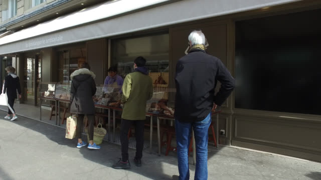 people in front of an open bakery a day after french prime minister edouard philippe announced that france will shut shops, restaurants and... - store opening stock videos & royalty-free footage
