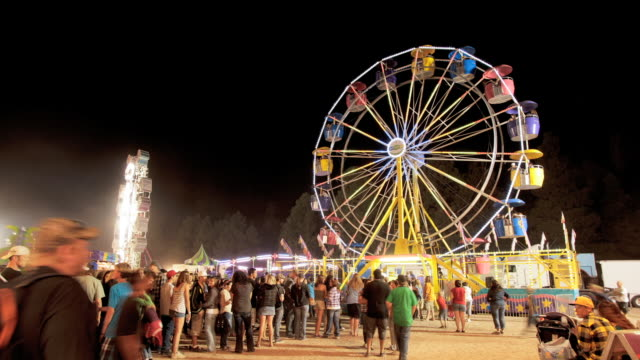vidéos et rushes de t/l ws people in front of ferris wheel at night / flagstaff, arizona, usa - fête foraine