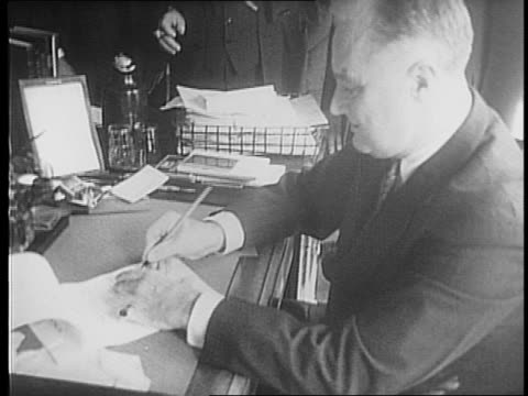 people in front of the white house / newspapermen in suits leave the white house / newspaper headlines on ickes / closeups of secretary ickes at desk... - anno 1941 video stock e b–roll