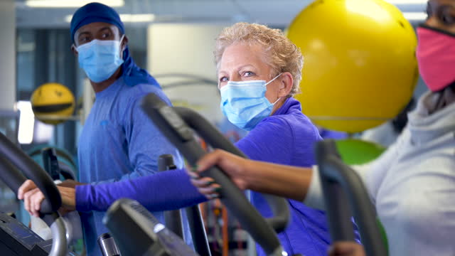 vídeos y material grabado en eventos de stock de personas en el gimnasio con entrenadores cruzados elípticos usando máscaras - gym