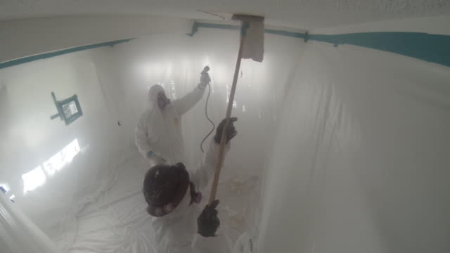people in hazmat suits removing asbestos from home, go pro wide shot - asbest stock-videos und b-roll-filmmaterial