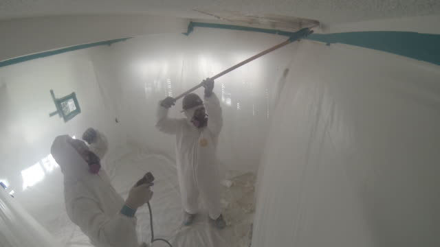 people in hazmat suits removing asbestos from home, go pro wide shot - removing stock videos & royalty-free footage