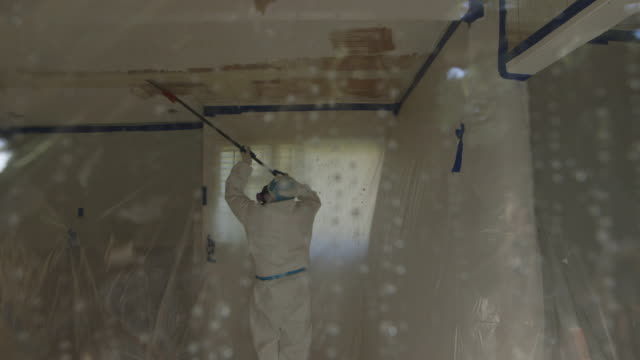 people in hazmat suits removing asbestos from home, wide shot through curtain - アスベスト点の映像素材/bロール