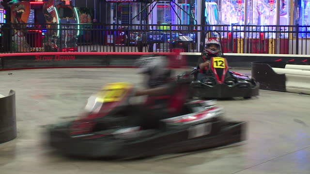 people in helmets driving indoor electric go-carts at accelerate indoor speedway & events in chicago on february 24, 2018. - go cart stock videos & royalty-free footage