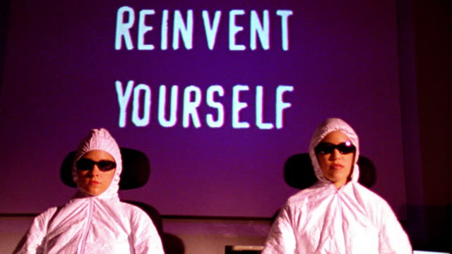 "2 people in hooded suits + sunglasses dancing in seats / ""reinvent yourself"" projected on wall in background - hood clothing stock videos & royalty-free footage"