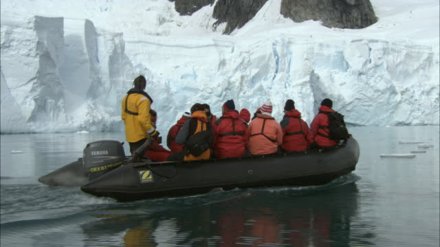 ms, people in inflatable raft approaching to large iceberg, paradise bay, antarctica - antarktis stock-videos und b-roll-filmmaterial