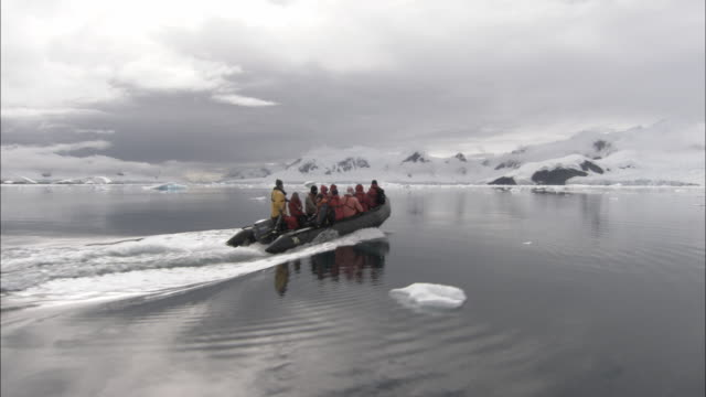 ms, people in inflatable raft traveling towards snow capped rocky mountains, rear view, antarctica - antarctica stock videos & royalty-free footage