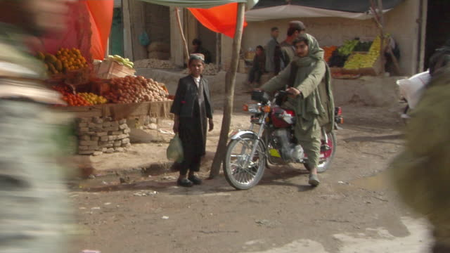 People in local market and soldiers passing by / Musa Qala Helmand Province Afghanistan
