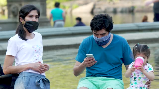 people in manhattan's central park new york city amid the outbreak of the coronavirus disease some wore a protective face mask and practiced social... - three people stock videos & royalty-free footage
