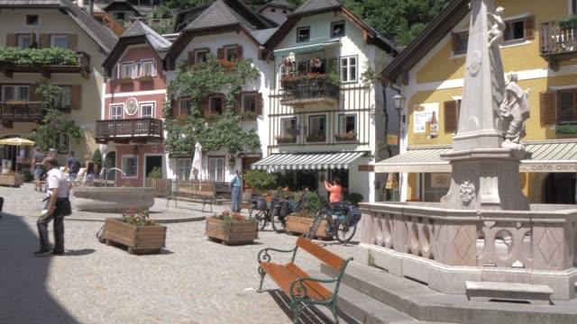 people in marktplatz in lakeside hallstatt village, unesco world heritage site, salzkammergut, austrian alps, austria, europe - courtyard stock videos & royalty-free footage