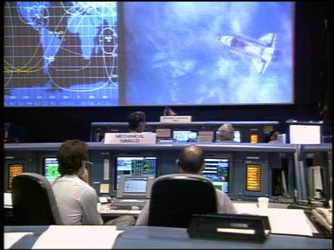 vidéos et rushes de people in mission control watching space shuttle fly over earth on screen / sts-84 - exploration de l'espace