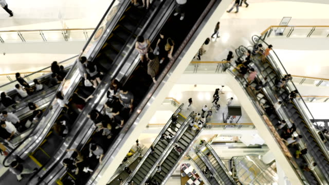 People in motion in escalators at shopping mall